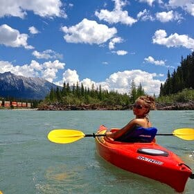 Registered veterinarian technician kayaking with a bright blue sky behind her