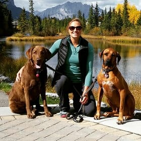 Veternarian kneeling on a dock with two large brown dogs beside her